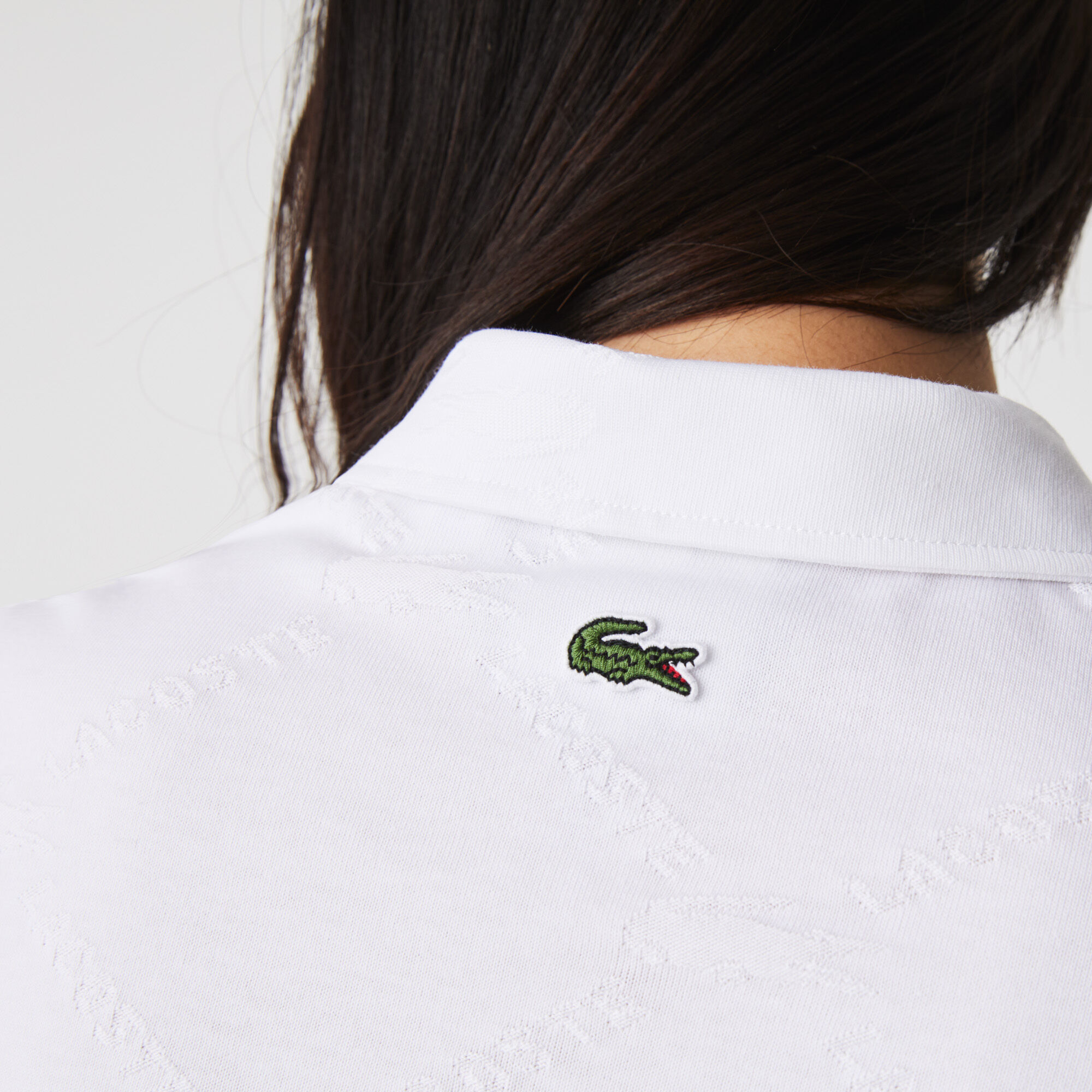 قميص بولو بأنماط مونوغرام وقصة ضيقة مجموعة Lacoste LIVE للنساء